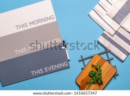 Flat lay of proactive moms kitchen workspace with cutting board and notes #1616657347