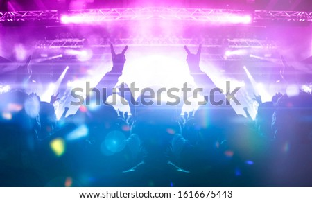 Image shot during a music festival. Light comes from a stage with a band show, people silhouettes are visible in front of it. #1616675443