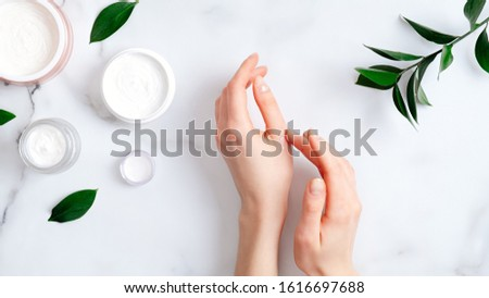 Cosmetic cream on female hands, jars with milk swirl cream and green leaves on white marble table. Flat lay, top view. Woman applying organic moisturizing hand cream. Hand skin care concept #1616697688