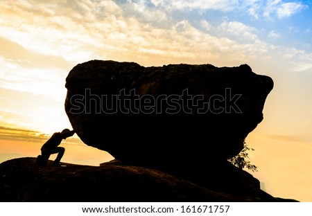 Hard work.The person rolls the rock on mountain. Royalty-Free Stock Photo #161671757