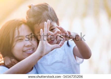 Asian mother and daughter making heart shape with hands together with love in the field with sunlight