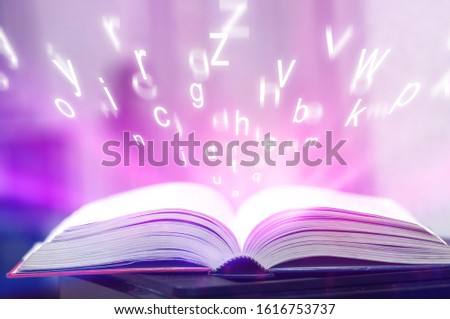 Open book on the table and english alphabet floating above the book in the library and blurred bookshelf  background. education background. back to school concept. #1616753737
