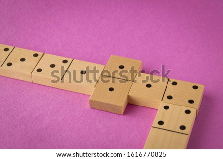 Playing dominoes on a purple background. Leisure games concept. Domino effect #1616770825