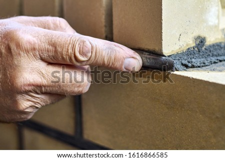 Bricklayer builds new fence from facing bricks. Alignment of inter-brick joints #1616866585