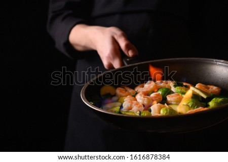 Professional cook cooks shrimps with vegetables on fire. Cooking seafood #1616878384