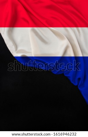 national flag of the modern state of the Netherlands folded onto black blank, concept of tourism, economy, politics, emigration #1616946232