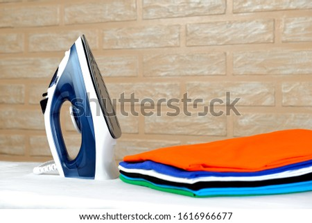 New modern electric steam iron and a stack of ironed t-shirts of various colors on ironing board on a brick wall background #1616966677