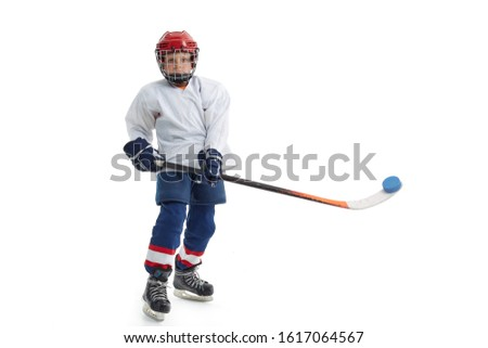 Junior ice hockey player . Child (boy) is hockey player in uniform with full equipment isolated on white background. Concept of children's sport, winter sport, healthy lifestyle. #1617064567