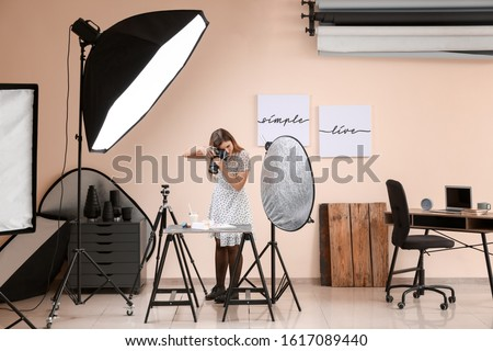 Young woman taking picture of macarons and milk in professional studio