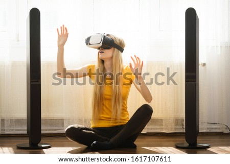 Young woman wearing virtual reality goggles vr box with arms outstretched sitting on floor in living room, listening to music. Connection, technology, new generation and progress concept. #1617107611