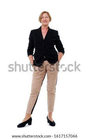 Elegant casually dressed senior woman with brown hair aged 55-60  standing and looking at camera, holding hands in pockets with beautiful toothy smile. Concept of lifestyle. Isolated on white #1617157066