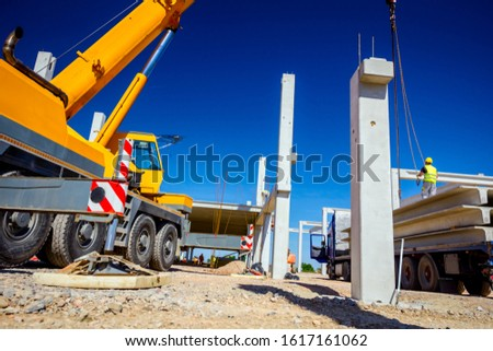 Worker is preparing crane hook for unloading concrete joist from truck trailer. #1617161062