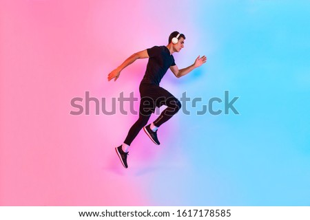 Sports man jumps. Photo of an active man in sportswear on a bright neon background. Dynamic movement. Side view. Sports and healthy lifestyle #1617178585