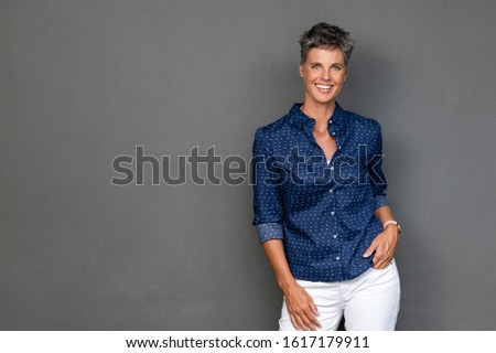 Happy mature businesswoman standing on grey background. Successful senior business woman with hand in pocket looking at camera. Portrait of confident and reliable lady standing against gray wall. #1617179911