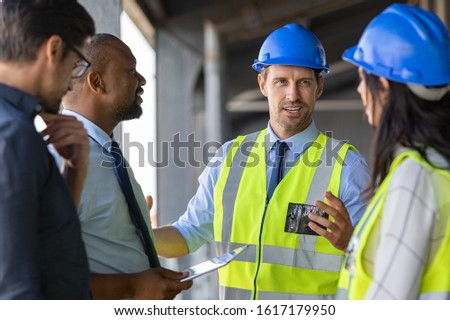 Happy mature engineer discussing the structure of the building with architects colleague at construction site. Engineers wearing safety hardhat having work conversation on the safety of the structure. Royalty-Free Stock Photo #1617179950