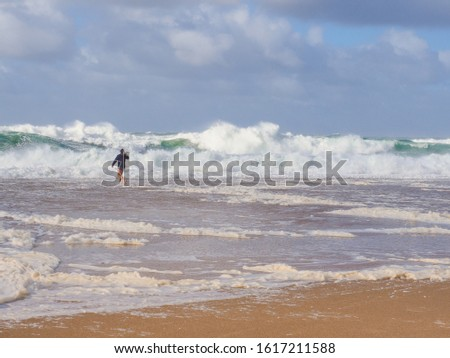 Stormy Atlantic ocean. Young man runs on sandy beach, near big, powerful, foamy waves. North Beach of Nazaré or Silver Coast, phenomenal underwater canyon, popular surf route in Europe, Portugal. #1617211588