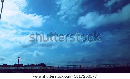 Clear skies, clear blue, with a few clouds streaking, just enough to water the sky, making a contrast to the head of the bridge. Nature vs. Human construction.   #1617258577