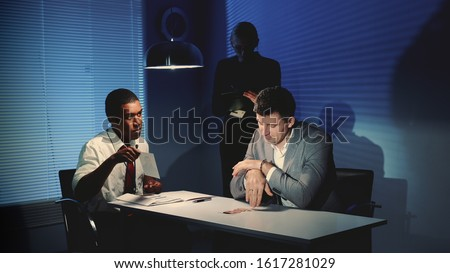 African police detective showing pictures of suspected robber's accomplice. In the background there is a female detective writing notes of the interrogation.