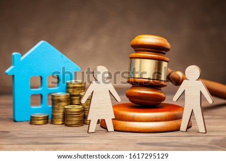 Divorce by law. Division of property after a divorce. The husband is trying to sue his wife for property under the law. A woman with a house and money, and a man with a hammer of a judge. #1617295129