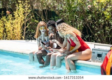 group of people of different ethnicities in swimsuits looking at the mobile phone at the edge of a pool #1617313354