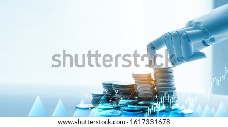 AI(Artificial Intelligence) and Financial Technology concept.Robot Hand Stacking pile of Coins,Financial technology,Stock chart,Investment,Fintech on white background.