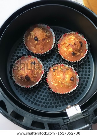 The air fryer basket and muffin with nuts and chocolate chips on white table background. Muffins baked with air fryer.Muffins are baked. #1617352738
