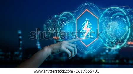 Energy and  power plant concept.Human hand holding a icon electric bolt on blurry bokeh power plant background.Industry 4.0 concept image. Royalty-Free Stock Photo #1617365701