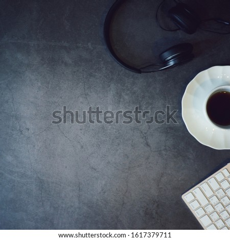 top view headphone, white coffee cup and keyboard with copy space at left, square pic