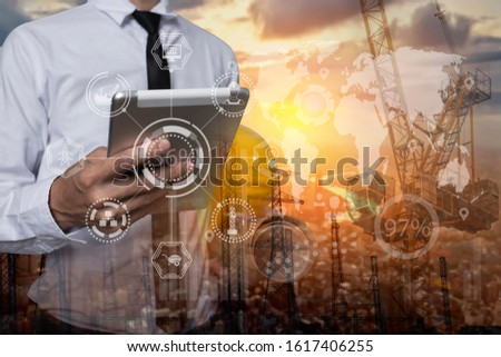 Double exposure of engineering using tablet digital technology interfaces icon with construction cranes and hight voltage electric towers during sunset background. #1617406255
