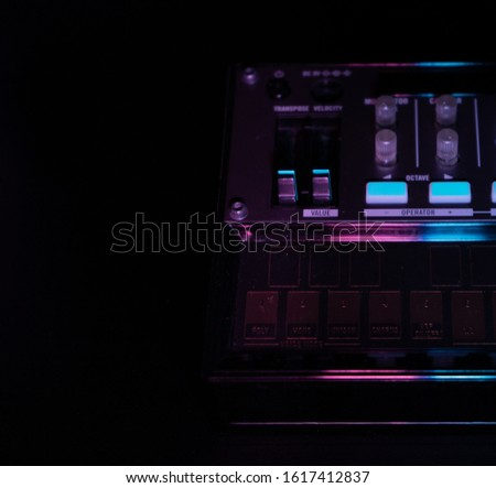 Small analog fm modulation synthesizer close up, selected focus, with knobs and faders, with effects arpeggiator and sequencer, colored lighting, black background, copy paste, music producer concept #1617412837