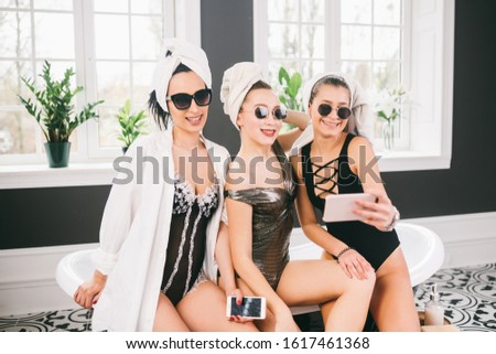 Picture showing group of happy friends in spa. girls with towels on heads having fun and taking selfie at home. Friendship, cosmetic, slumber party concept. Hen party with a bride in hotel.