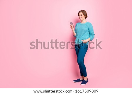 Full length body size view of her she nice attractive pretty lovely cheerful brown-haired girl using cell chatting with boyfriend date web service isolated over pink pastel color background