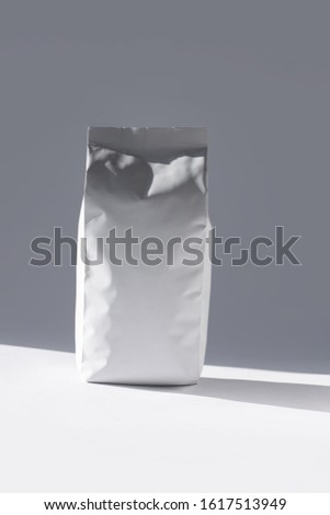 Blank foil food or drink bag on white background in minimal style with natural light shadow. Monochrome photo. Packaging with valve and seal template mockup. Metallic coffee tea retail package design. #1617513949