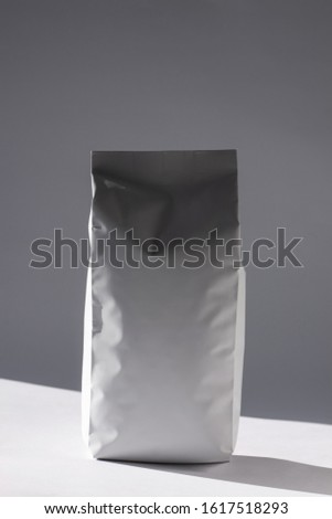 Blank foil food or drink bag on white background in minimal style with natural light shadow. Monochrome photo. Packaging with valve and seal template mockup. Metallic coffee tea retail package design. #1617518293