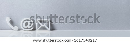 White Popular Contact Web Icons On Desk Over The Reflective Desk Against Gray Wall