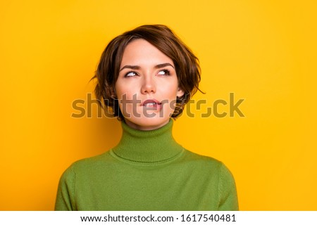 Closeup photo of amazing short hairdo lady biting lips looking up empty space have doubts deep thinking wear casual green turtleneck warm isolated yellow color background