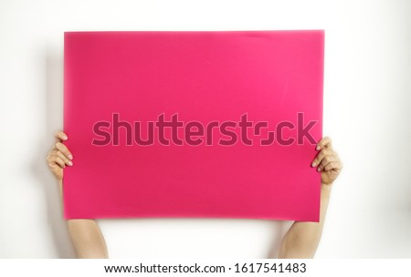 A large sheet of red paper in hands on a white background. Copy space. Woman hold blank card.   Royalty-Free Stock Photo #1617541483