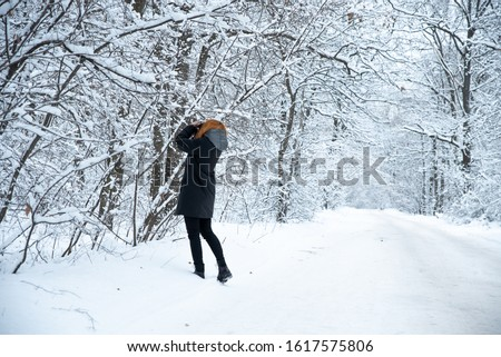 A girl takes pictures of winter nature in the forest. She has red hair and is not cold. White snow-covered forest, Park, road #1617575806