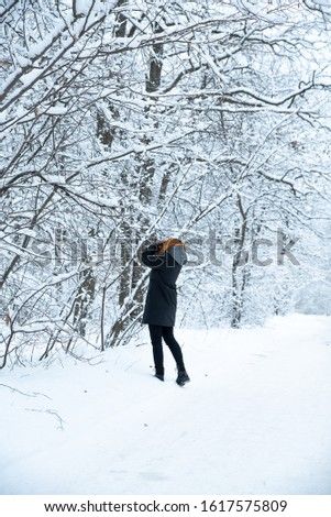A girl takes pictures of winter nature in the forest. She has red hair and is not cold. White snow-covered forest, Park, road #1617575809