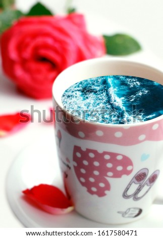 White cup with water. Sea. Ocean. Sea waves. Creative postcard. #1617580471