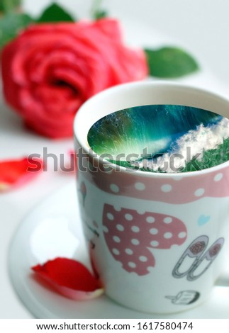 White cup with water. Sea. Ocean. Sea waves. Creative postcard. #1617580474
