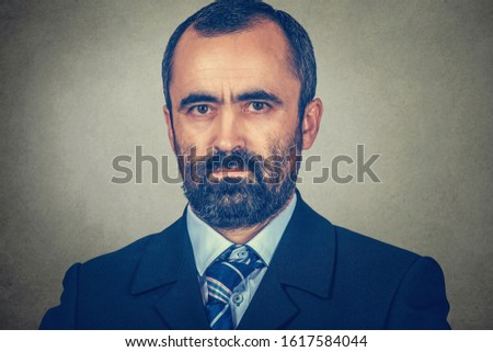 Portrait closeup of a serious middle-aged mature man looking at you camera seriously. Mixed race bearded model isolated on gray studio wall background with copy space. Horizontal image. #1617584044