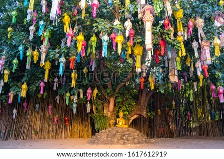 Wat Pa Dara Phirom Phra Aram Luang Chiang Mai Thailand Buddha sitting under a tree surrounded by lanterns #1617612919