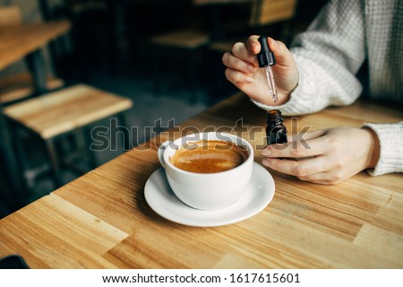Adding CBD oil in a coffee cup Royalty-Free Stock Photo #1617615601