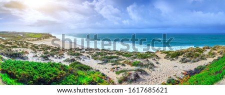 A ocean waves on the beautiful sand beach in at the cloudy stormy day. Breathtaking romantic panoramic seascape of ocean coastline. Praia d'el rey near Obidos Lagoon. Portugal. #1617685621