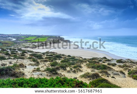 A ocean waves on the beautiful sand beach in at the cloudy stormy day. Breathtaking romantic seascape of ocean coastline. Praia d'el rey near Obidos Lagoon. Portugal. #1617687961