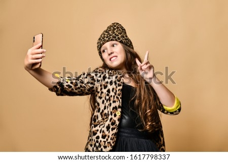 Young plus size girl with long hair in leopard colored clothing and accessories standing and making selfie with smartphone. she showing peace sign over pastel yellow wall background