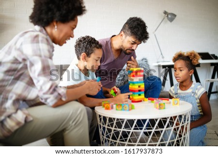 Family time. Young black parents with two kids playing together at home #1617937873