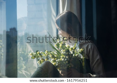 young girl sits on a windowsill, holds flowers, smiles and looks out the window with reflection effect, gloss effect #1617956251