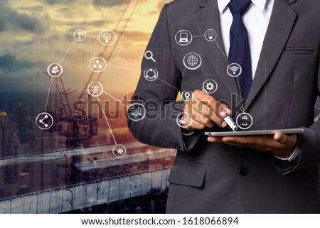 Double exposure business man using tablet and digital technology interfaces icon with construction cranes no city background. #1618066894